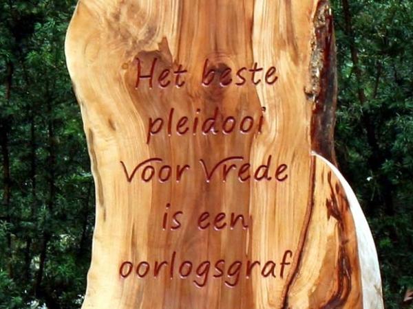 Oorlogsgravenmonument van hout met ingesneden tekst